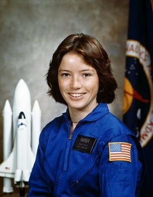Anna Fisher is a Whte woman. She is smiling in a blue NASA uniform