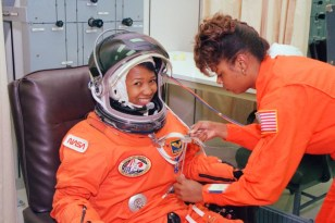Dr Mae Jemison is a Black woman. She sits and smiles while another Black woman in a NASA uniform arranges wires on her suit