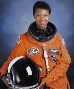 Dr Mae Jemison is a Black woman. She is smiling andwears an orange astronaut suit