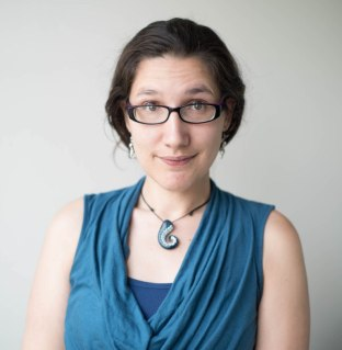 Mika McKinnon is white woman wearing glasses with a decorative necklace